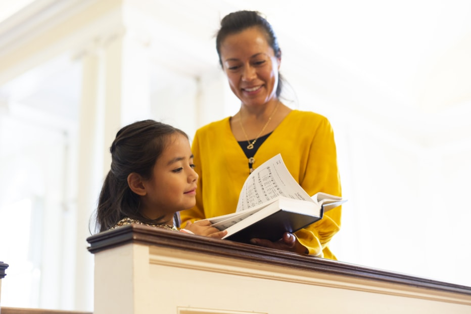 Mother and daughter hold hymnal
