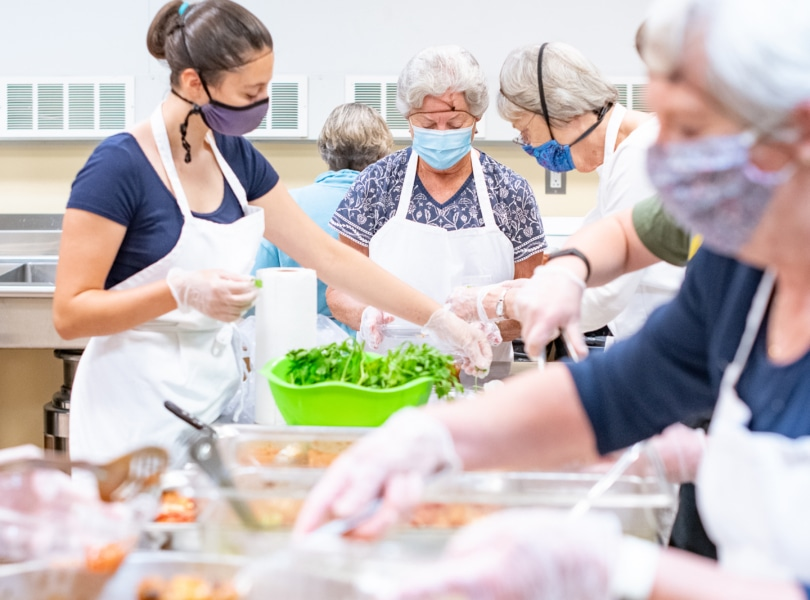 Volunteers prepare food for a free meal program