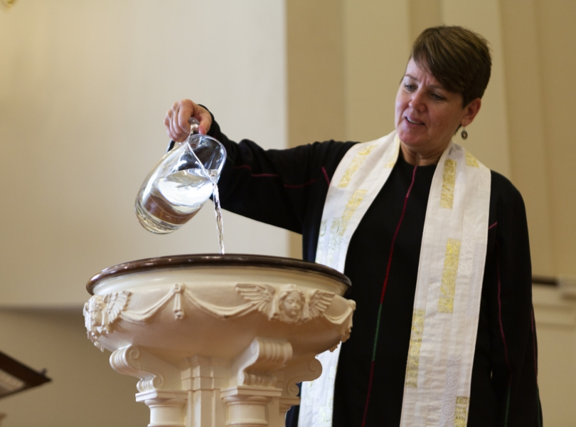 Pastor pours baptismal water