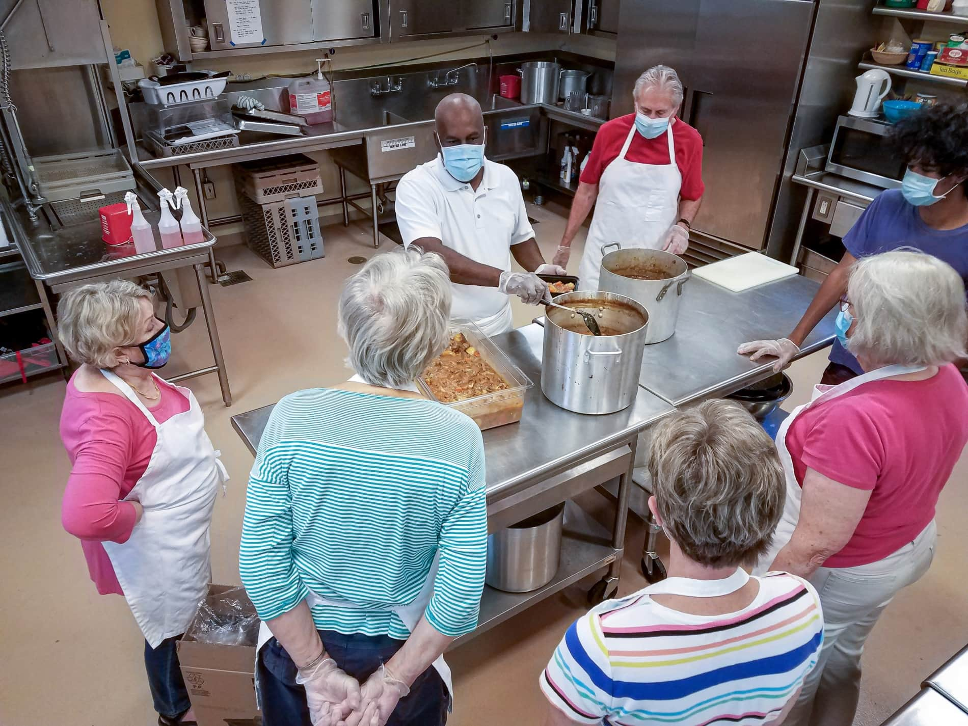 Volunteer gives cooking instruction to other volunteers