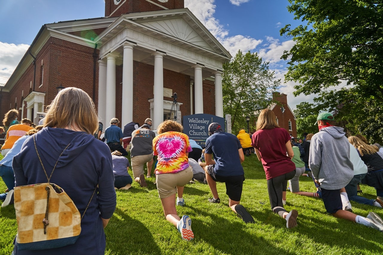 Congregants take a knee on the green of the Wellesley Village Church in support of racial justice