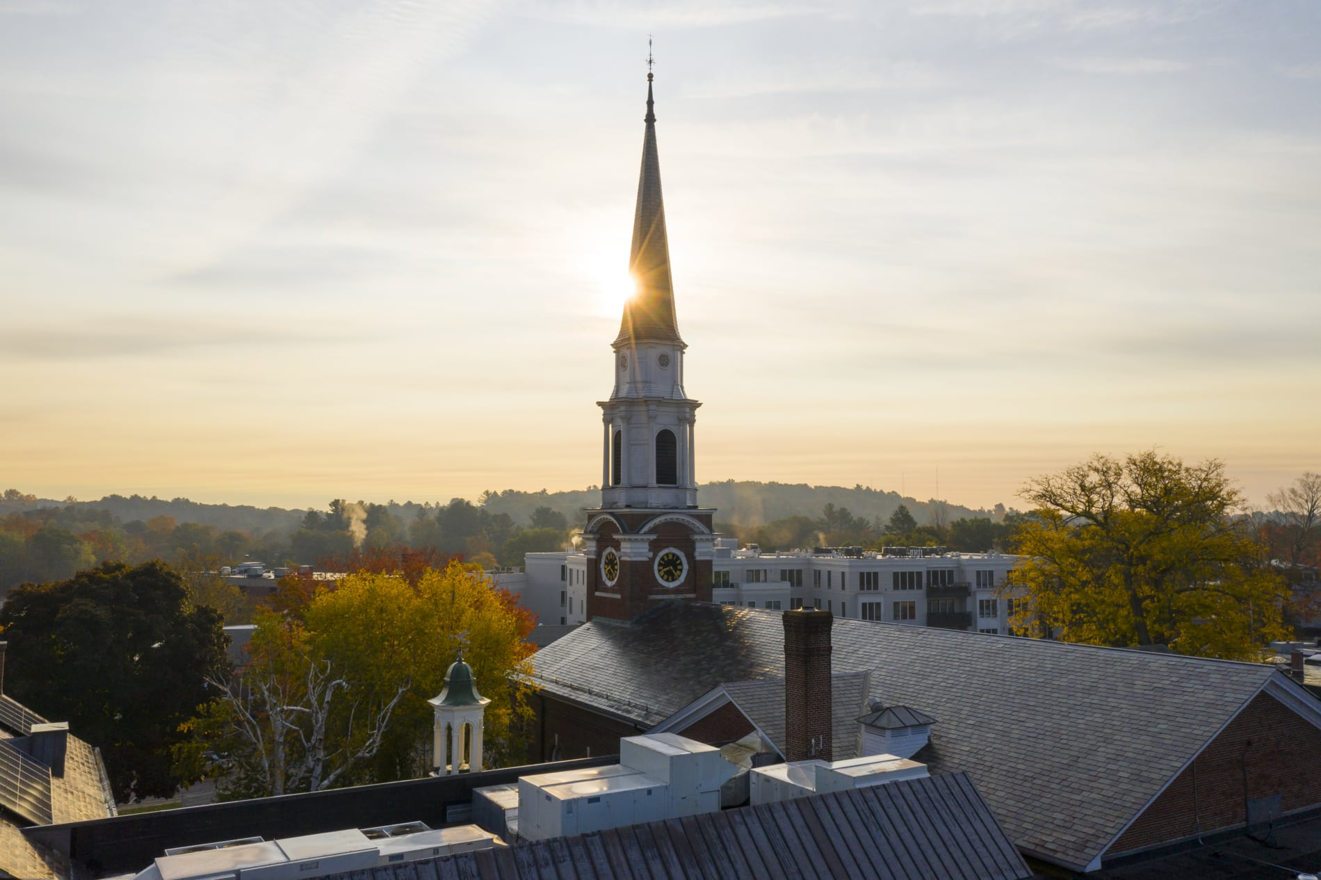 The steeple of the Wellesley Village Church towers over downtown Wellesley as the sun rises.