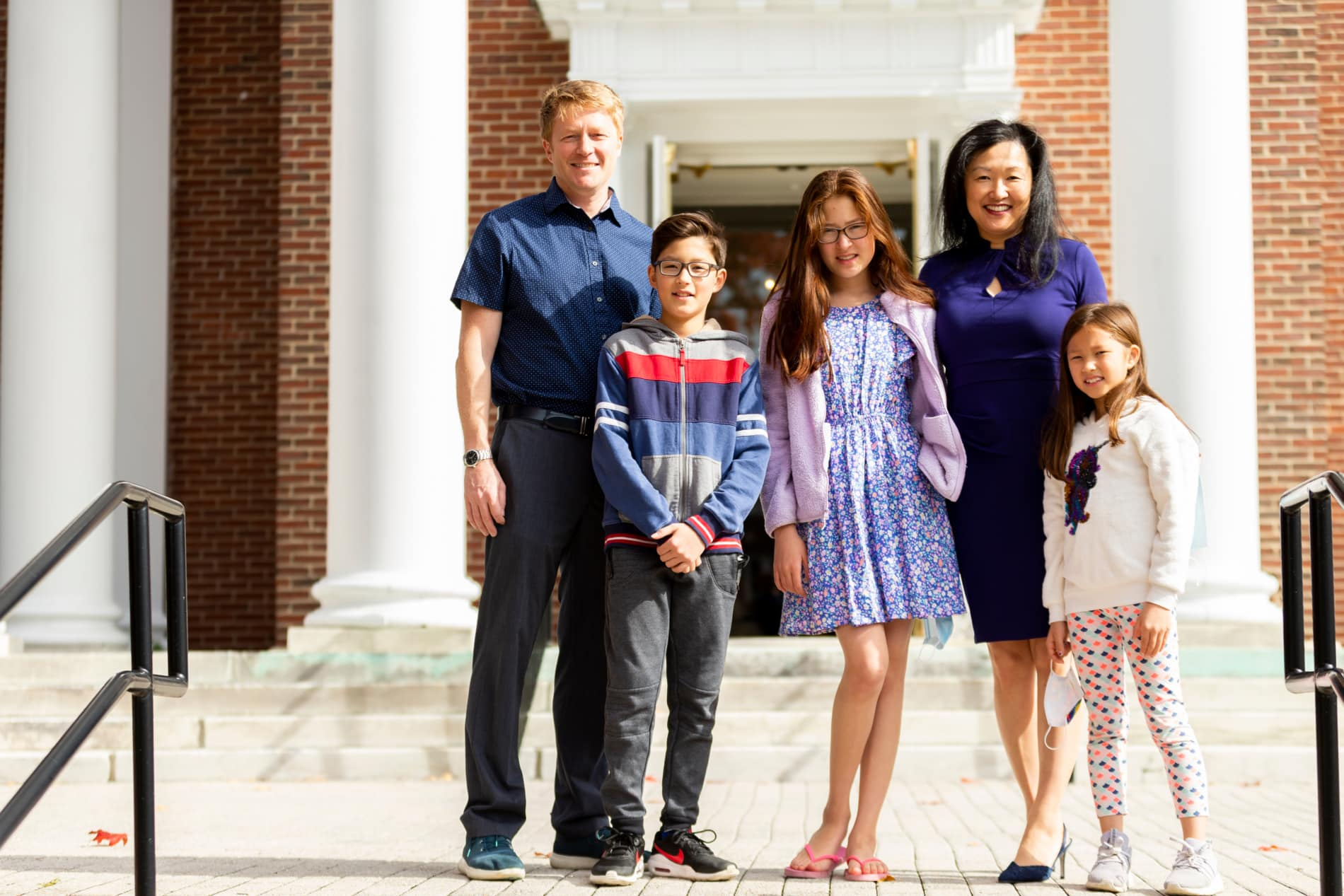 A multi-racial family of five stands on the steps of the Wellesley Village Church