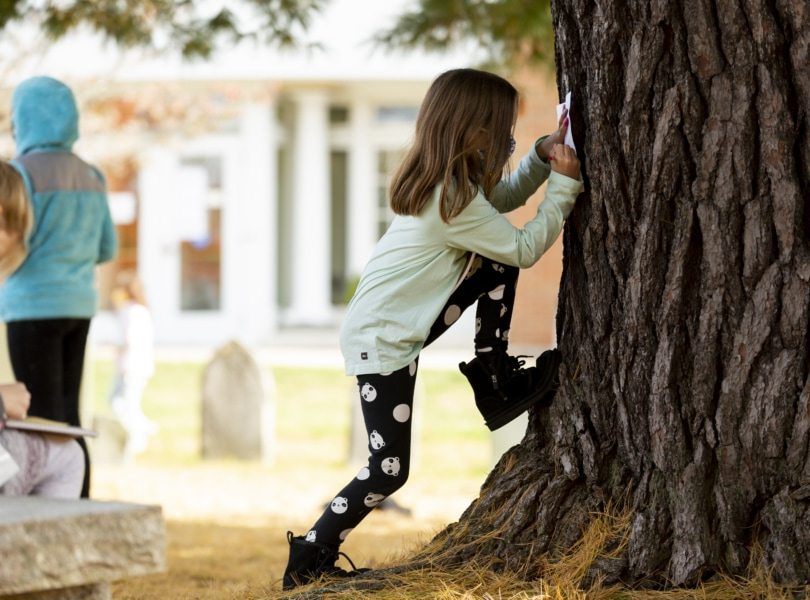 Child leans against tree
