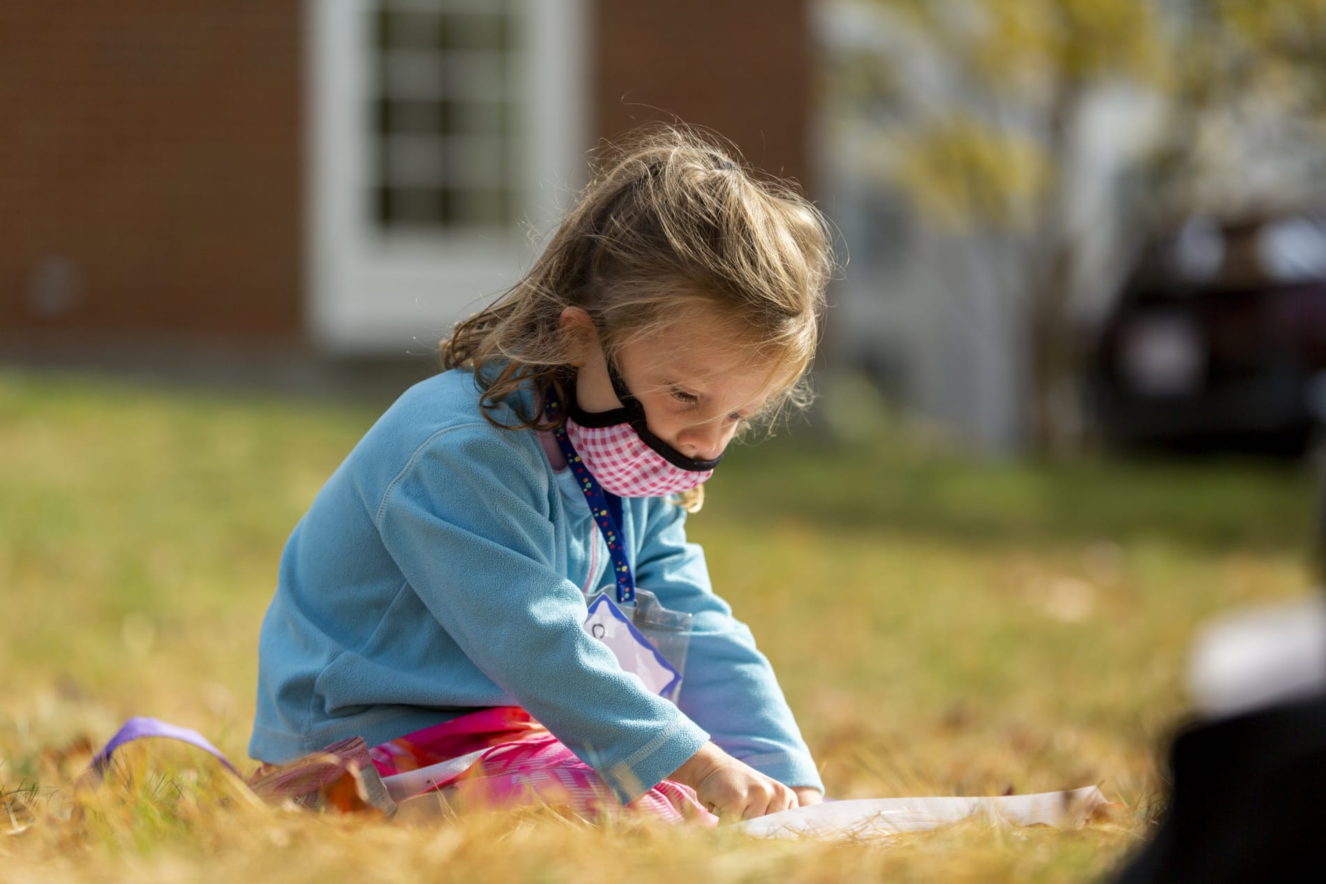 A young girl sits on the grass and colors