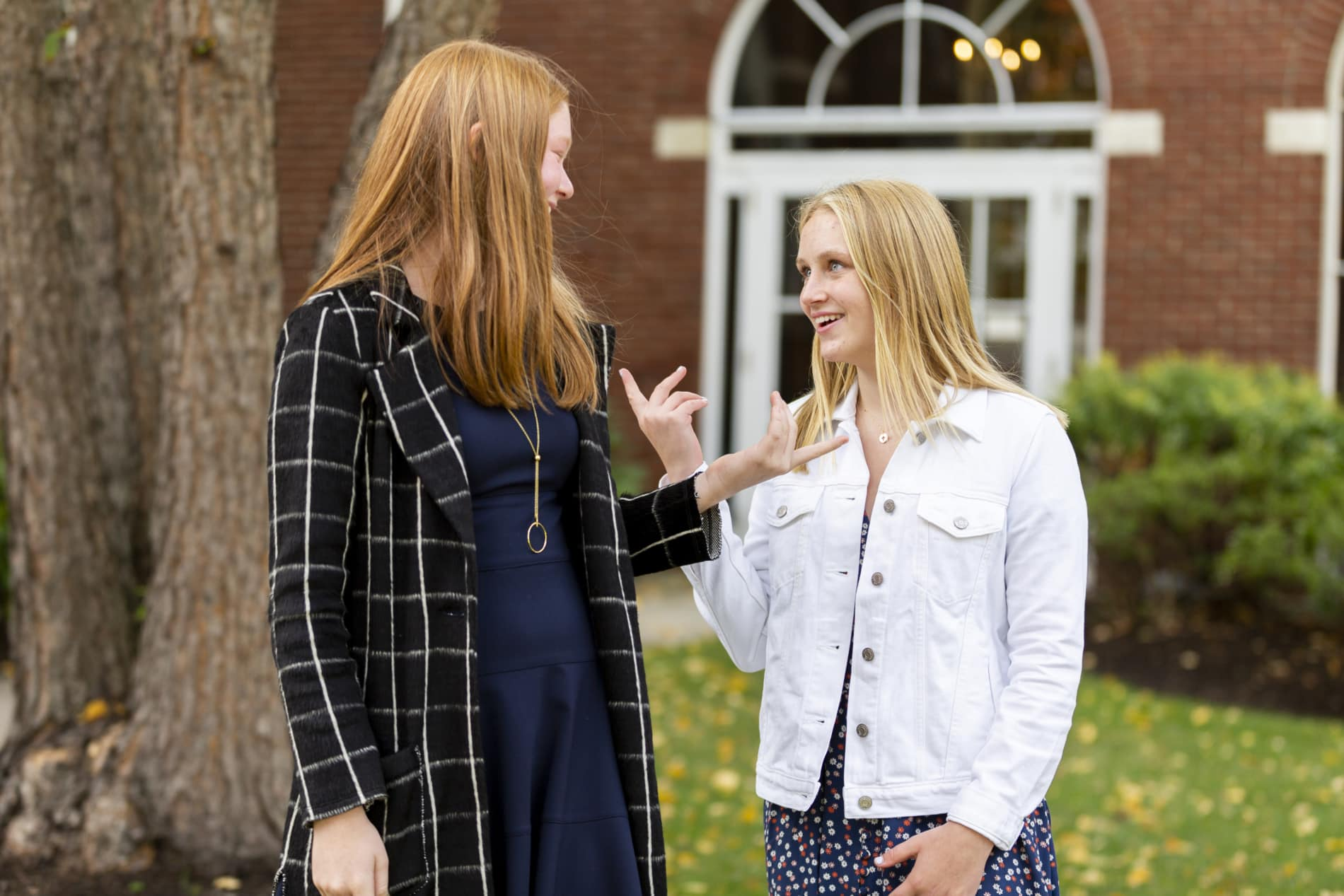 Two teenage girls talk outside of church