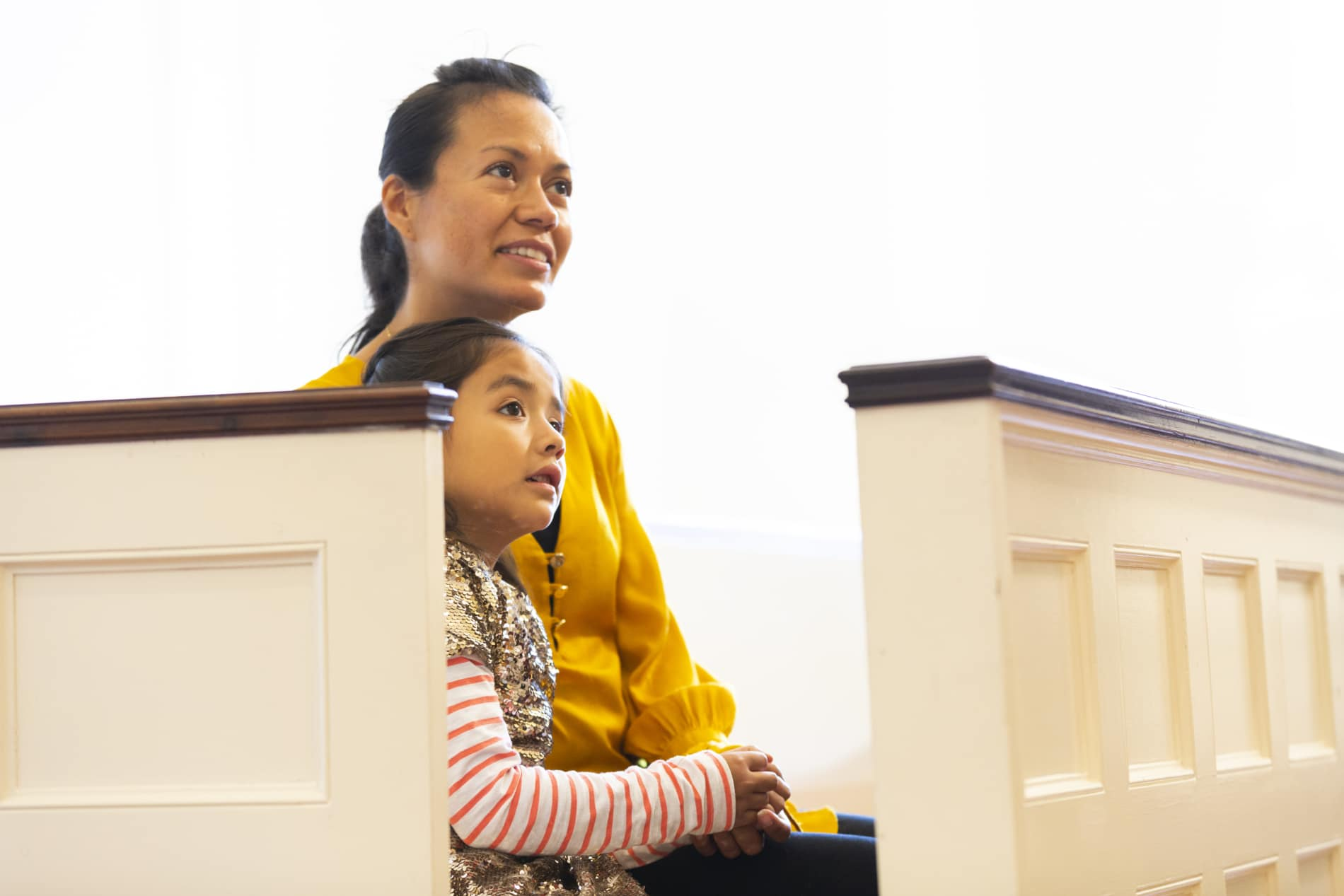 A mother and her young daughter seated in a pew