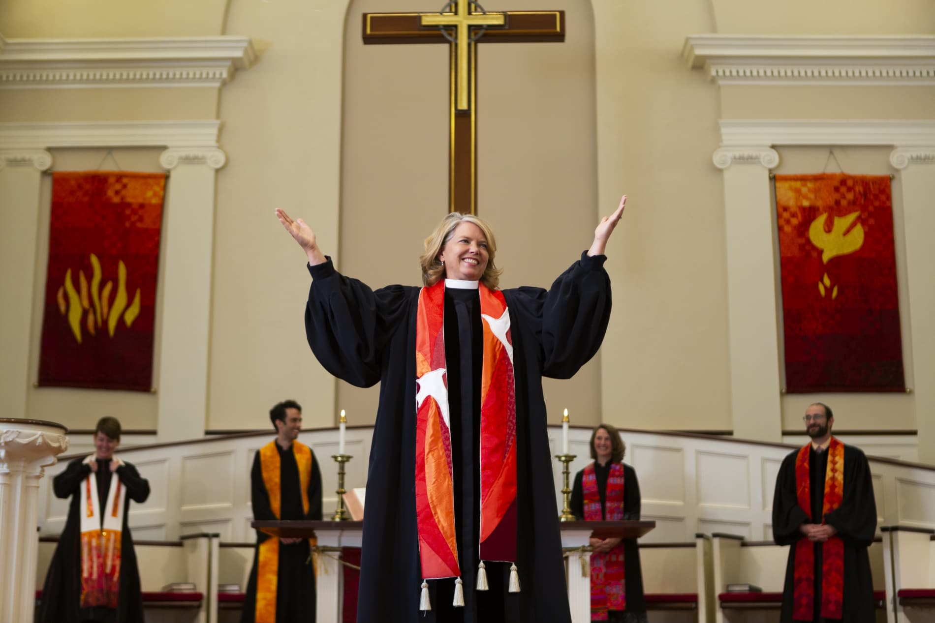 Rev. Sarah Butter lifts her hands to exhort the congregation in worship