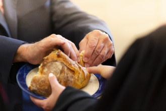 A man tears a piece of communion bread