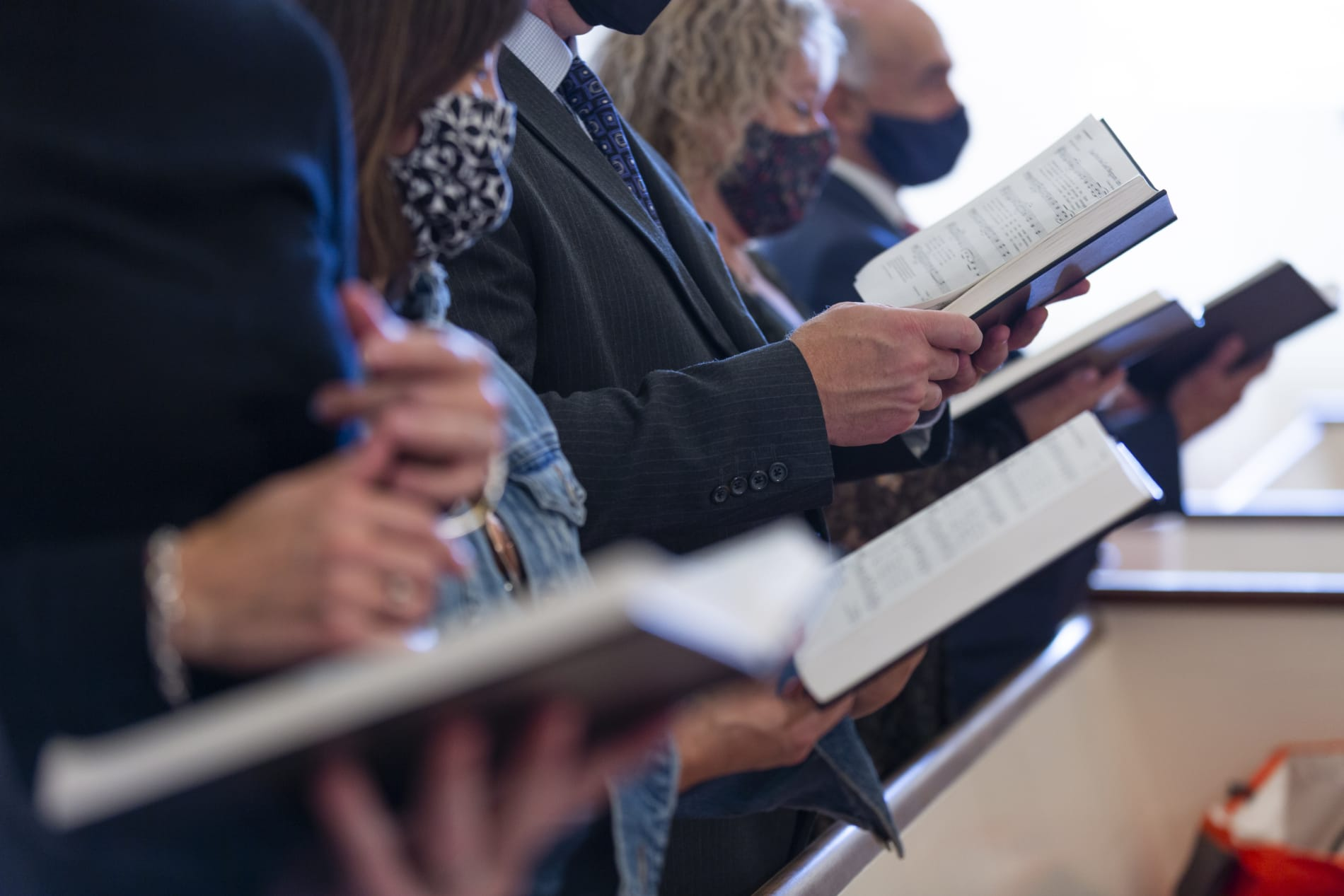 Congregants hold hymnals and sing
