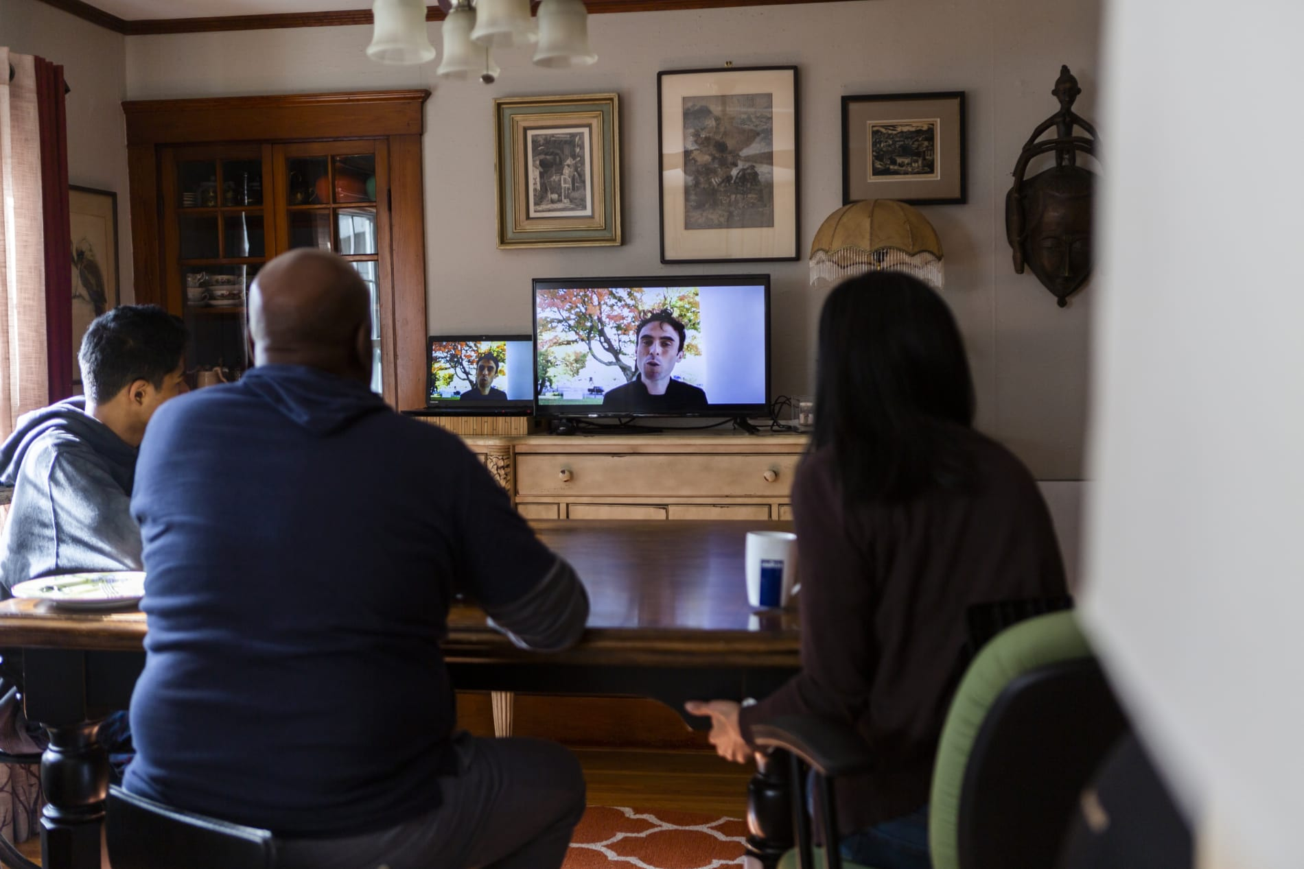 A family gathers in their living room to watch Wellesley Village Church's livestreamed worship service