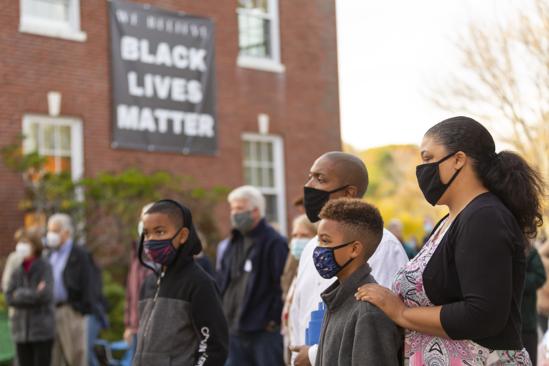 A Black family of four stands together with a Black Lives Matter sign in the background