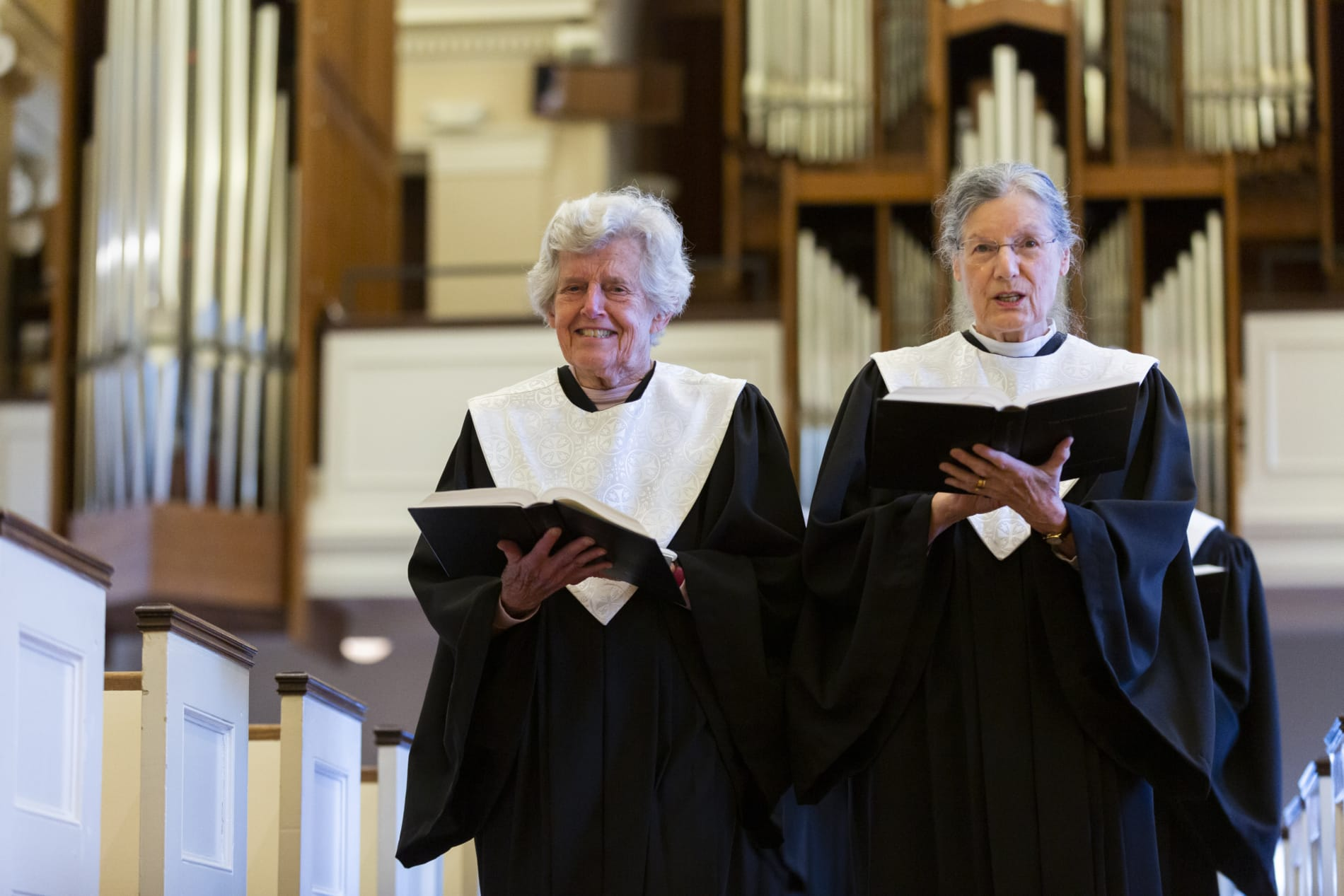 Two women sing in a processing choir