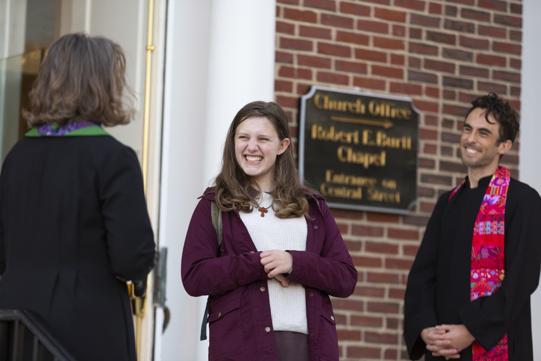 Two ministers greet a young woman as she arrives at church