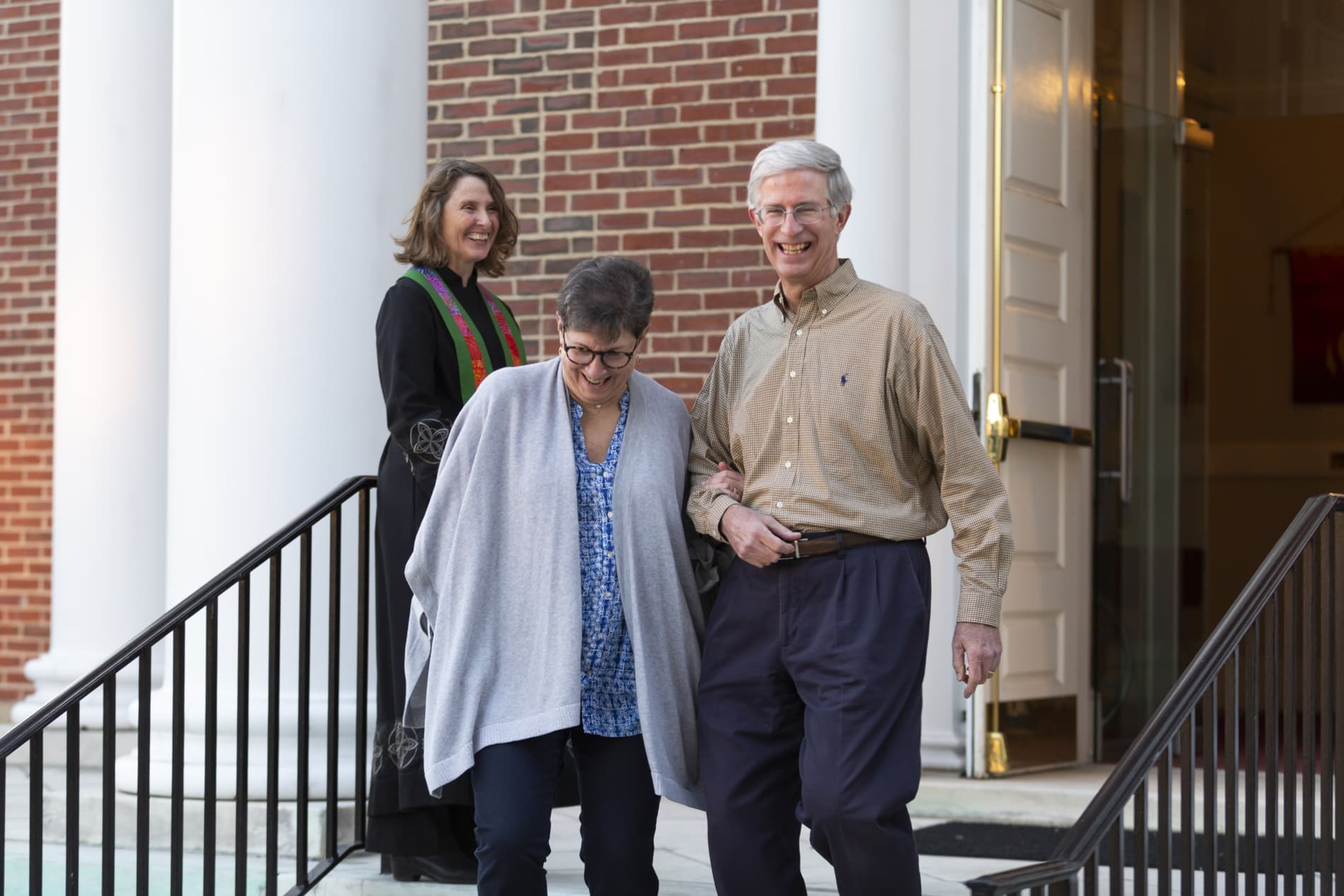 A smiling couple descends the stairs of the church while a pastor looks on