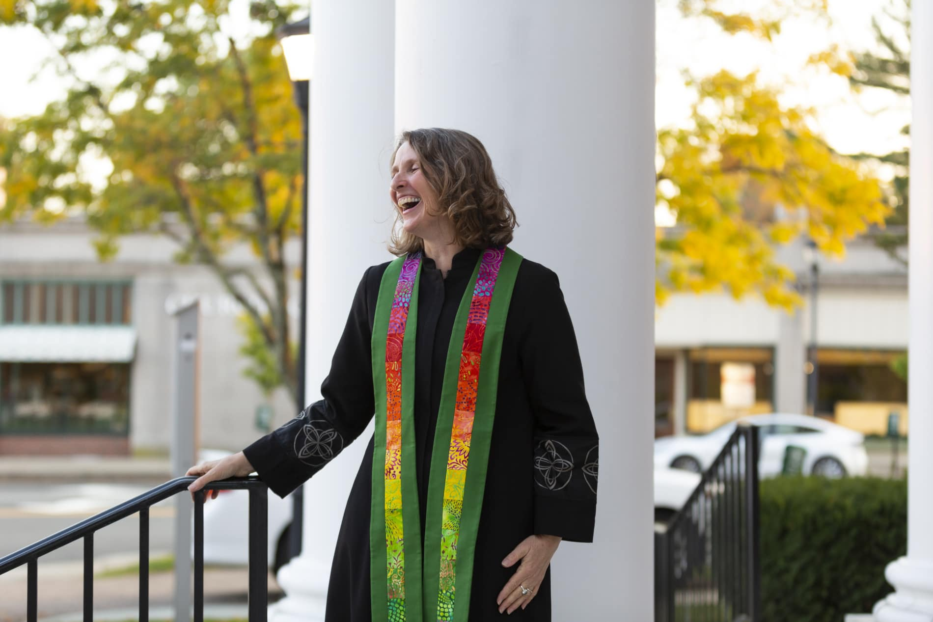 A pastor smiles as she greets people outside of church