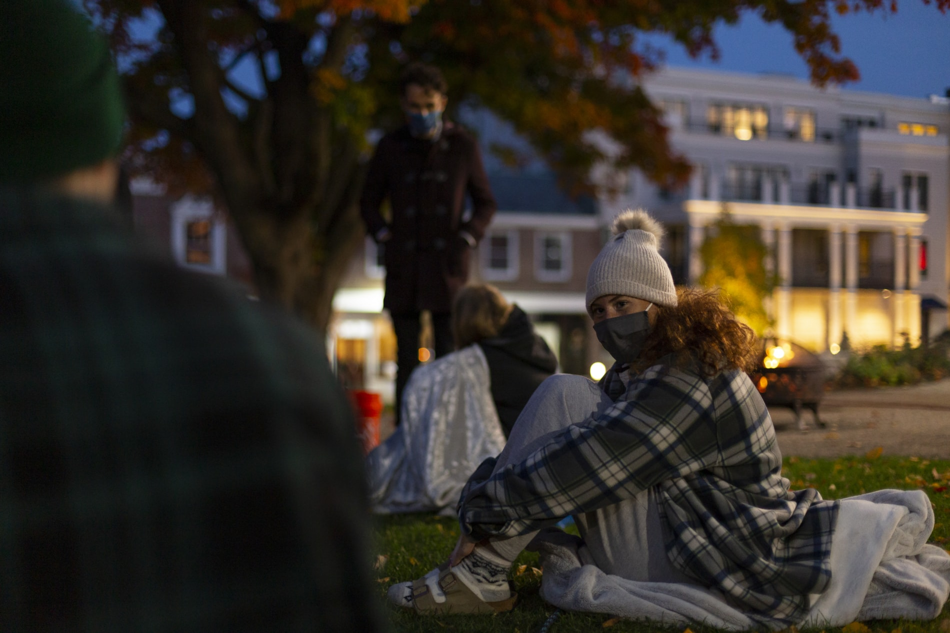 A teenage girl sits on the grass at an evening youth group event
