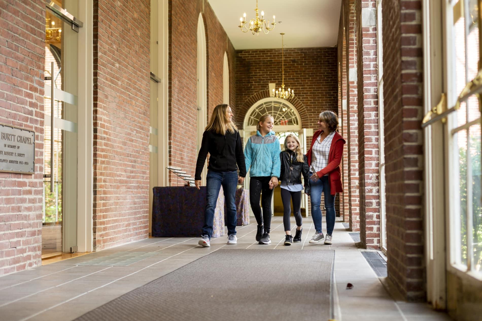 Family walks in church corridor toward sanctuary