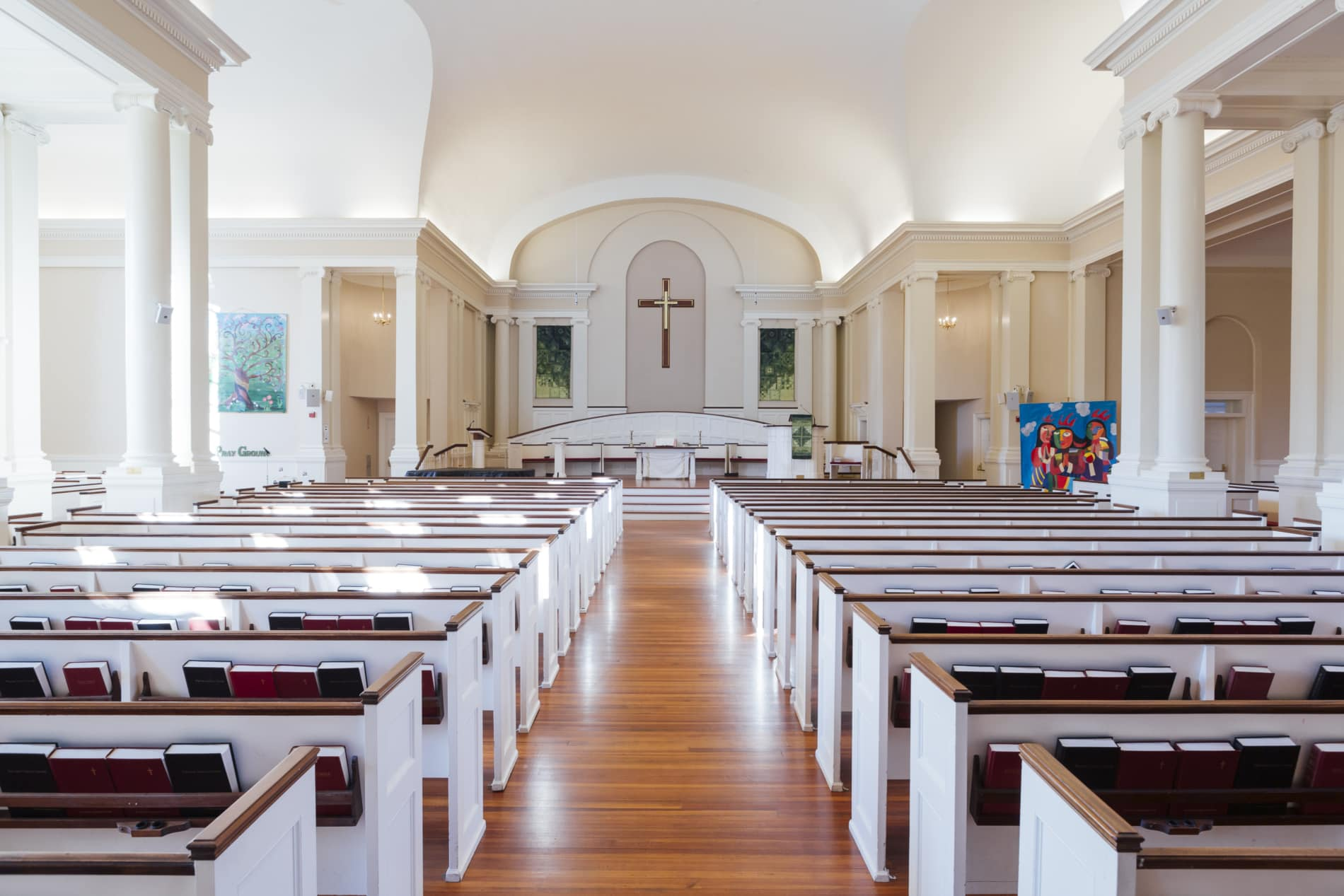 Sanctuary of the Wellesley Village Church showing communion table and large cross on the wall
