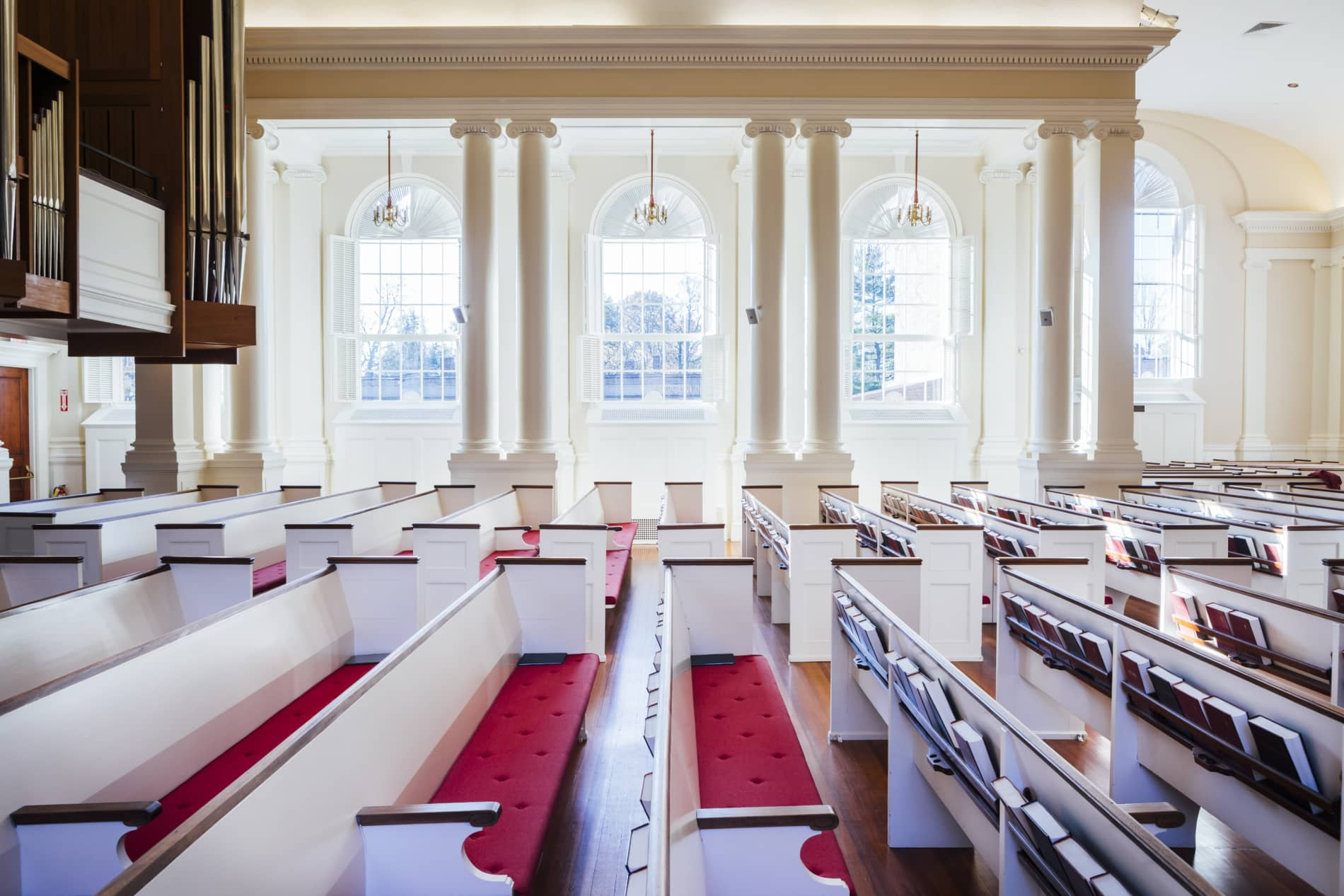 Interior of the sanctuary of Wellesley Village church showing pews, organ pipes, and clear glass windows.
