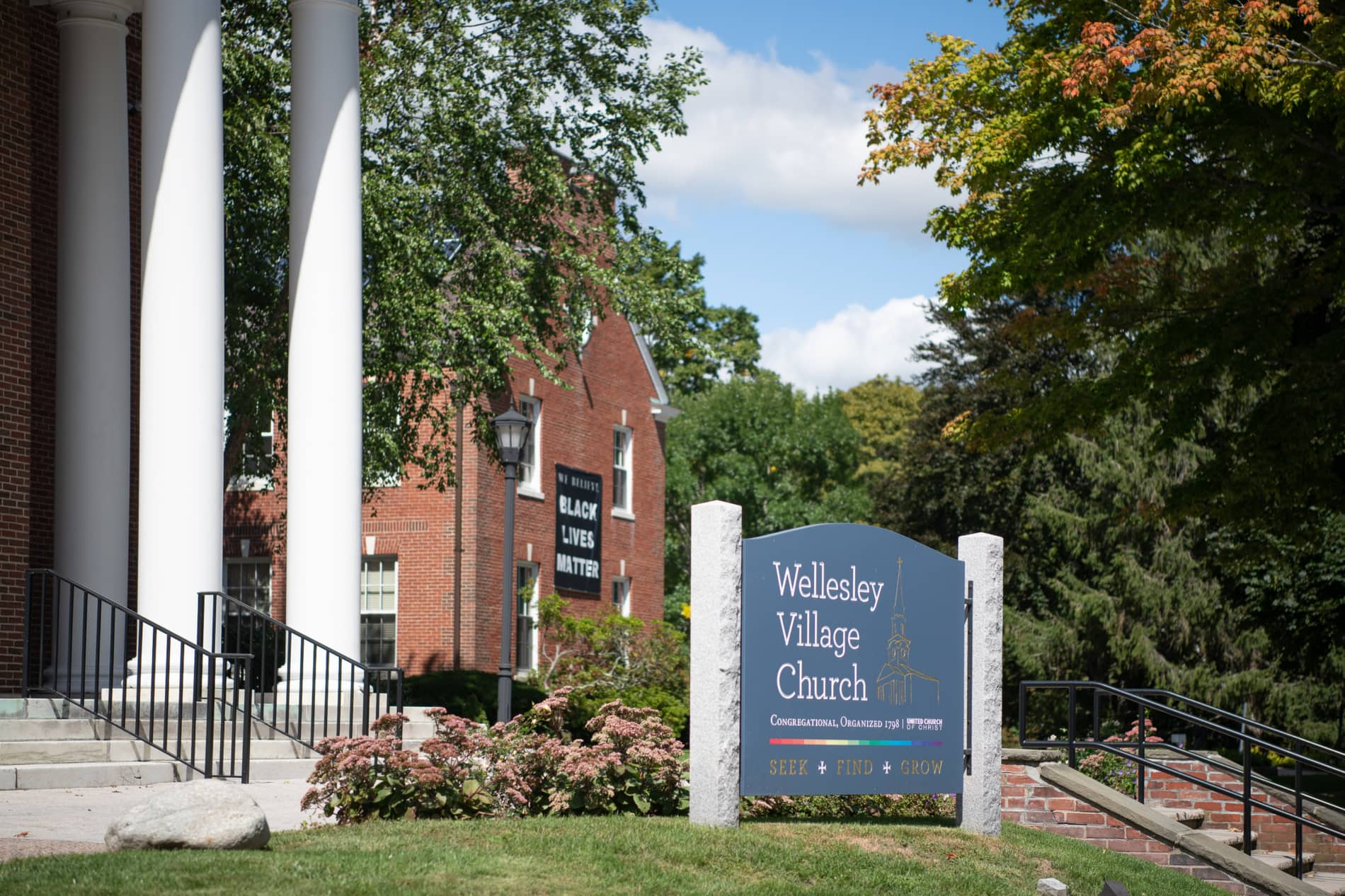 The exterior sign of the Wellesley Village Church with a Black Lives Matters banner in the background