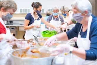 A group of folunteers preps a meal for the Village Table food program