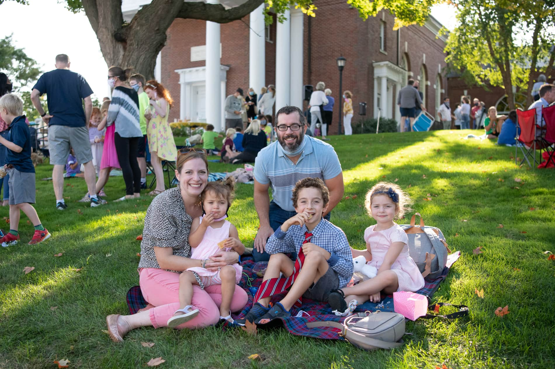A familyi of five sits on the green in front of the Wellesley Village Church