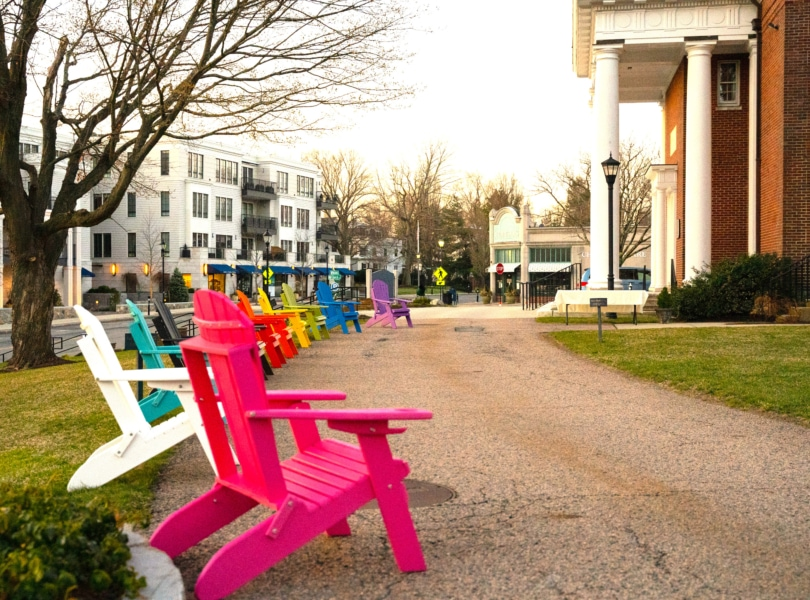 Rainbow-colored Adirondack chairs in cloister garden