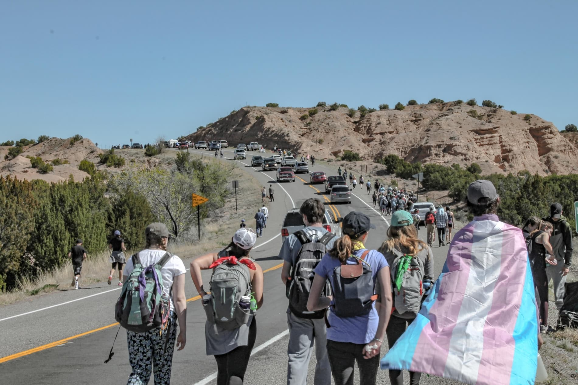 Church youth group travel up a road with a youth carrying flag of transgender symbol