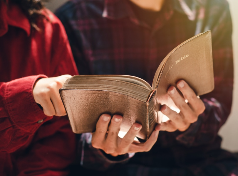 Two people are studying and reading the Bible.